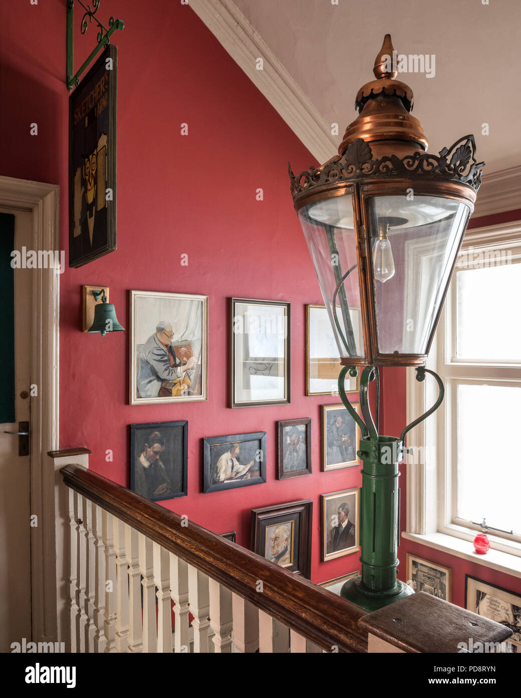Top of entrance hall staircase at the London sketch club. In the foreground is an old street lamp and the walls are adorned with assorted portraits - Stock Image