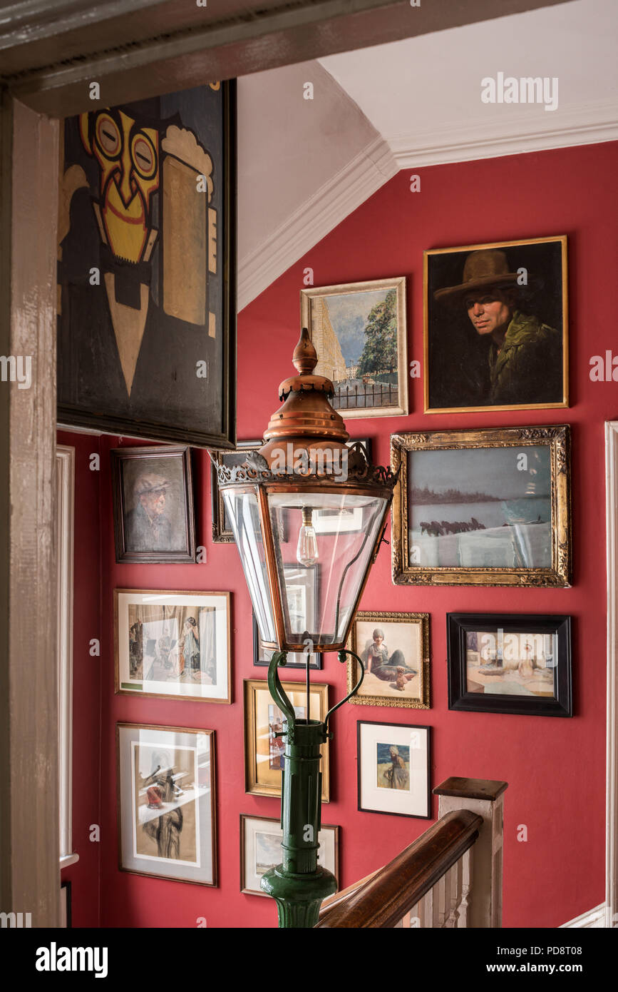 Assorted artworks on the wall of the london Sketch club staircase. A street lamp lantern is in the fireground - Stock Image
