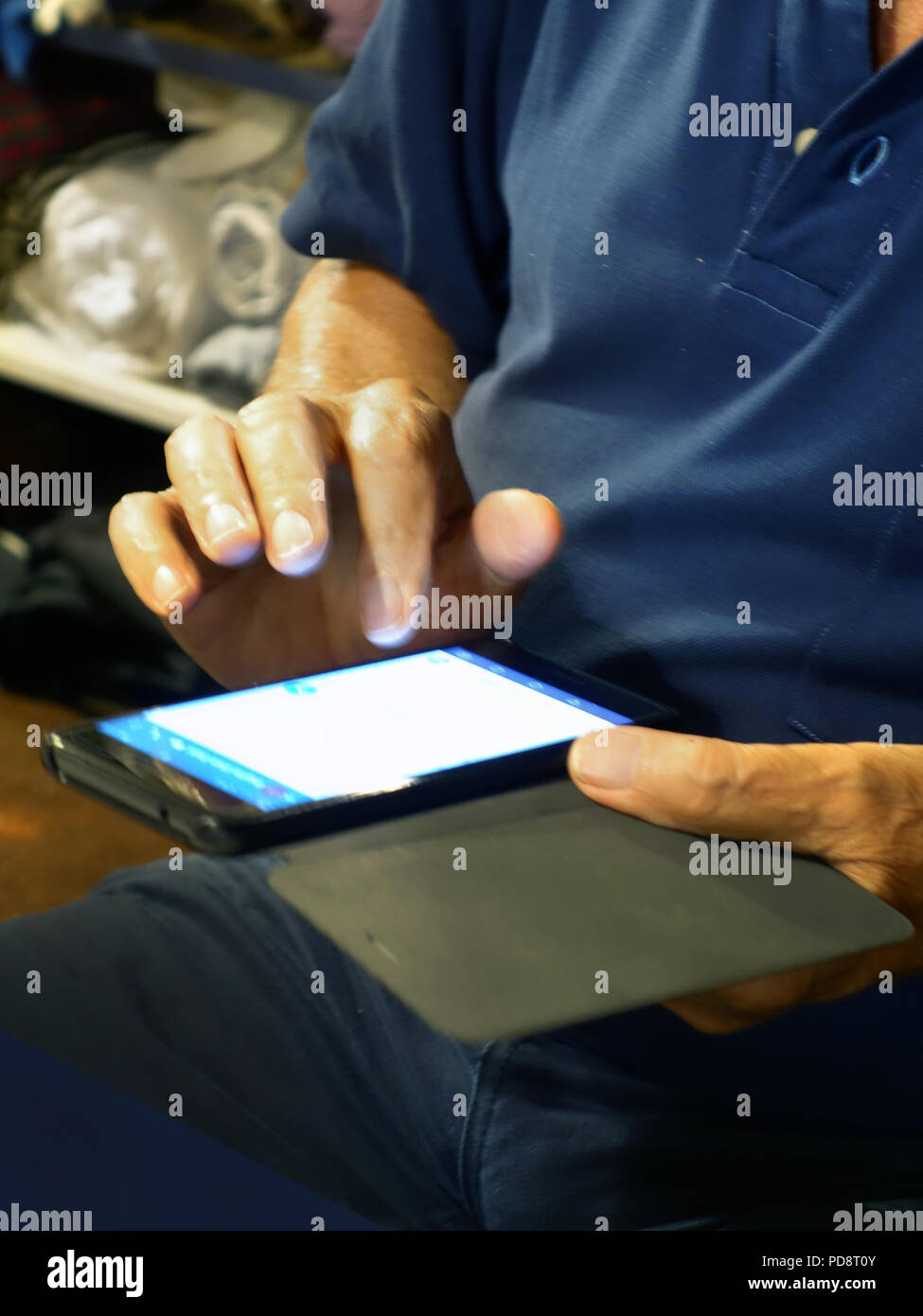 retired man using a smartphone indoors at night, seen typing on the touch screen. - Stock Image