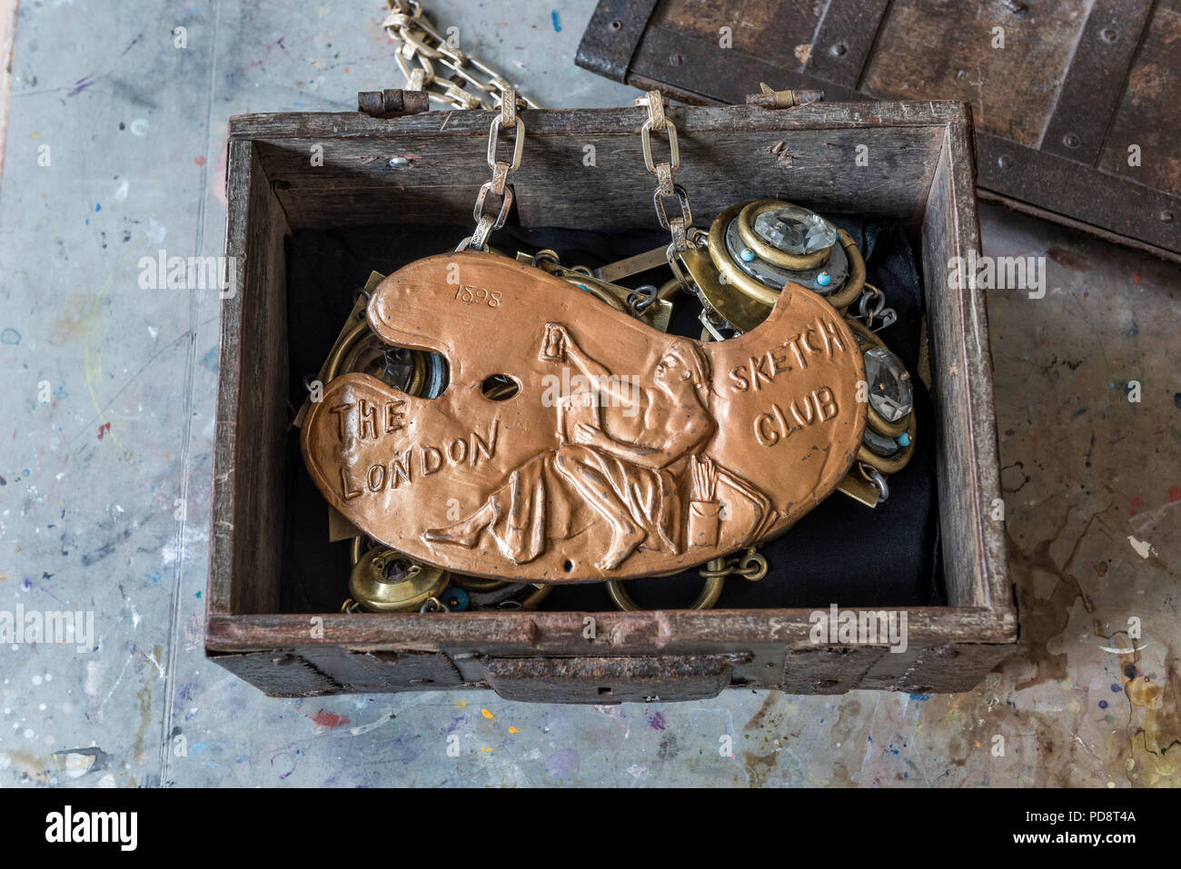 An old box of regalia containing a copper palette and an officers chain made from plumbing scraps and door knobs - Stock Image