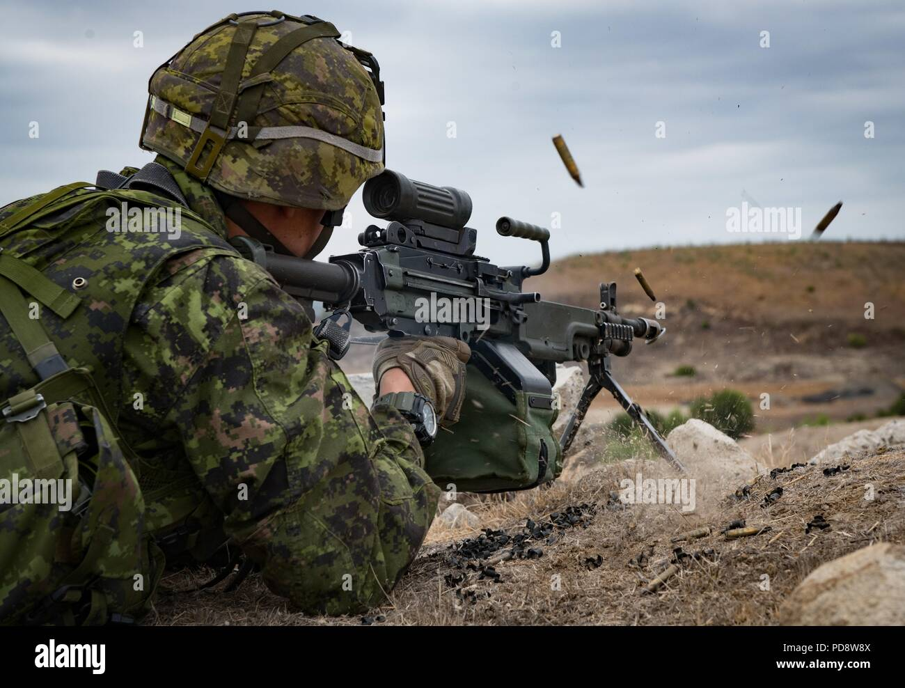 180703-O-N0842-3004 CAMP PENDLETON, Calif. (July 3, 2018) A member of the Canadian 2nd Battalion Royal 22e Regiment engages a target with his C9A2 Light Machine Gun in Combat Town Kilo-2 during the biennial Rim of the Pacific (RIMPAC) exercise on Marine Corps Base Camp Pendleton, July 3, July 3, 2018. Twenty-five nations, 46 ships, five submarines, about 200 aircraft, and 25, 000 personnel are participating in RIMPAC from June 27 to Aug. 2 in and around the Hawaiian Islands and Southern California. The world's largest international maritime exercise, RIMPAC provides a unique training opportuni - Stock Image