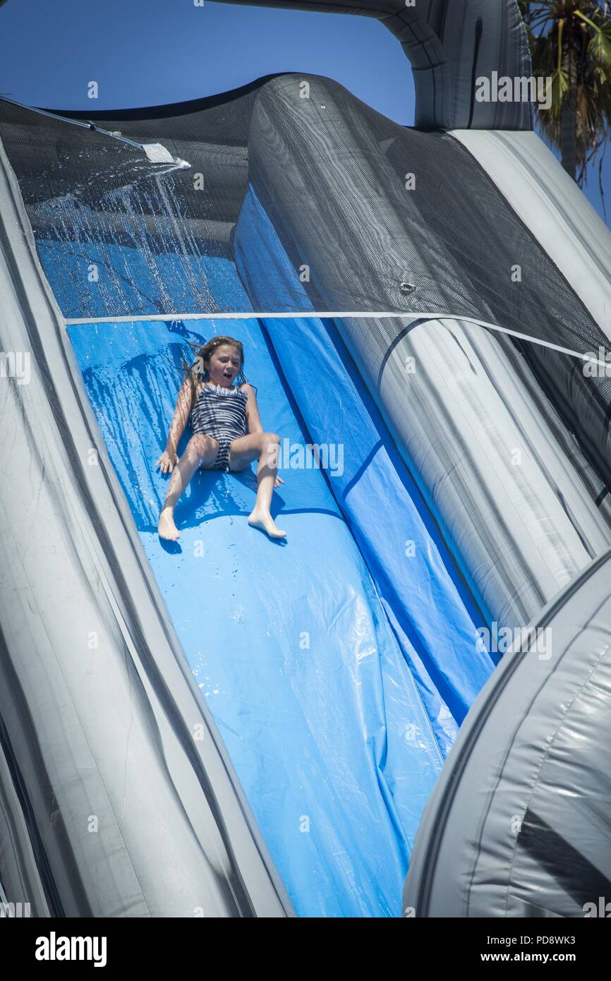 A girl slides down a waterslide in the family fun zone at the Fourth of July Beach Bash on Marine Corps Base Camp Pendleton, California, July 4, 2018, July 4, 2018. The beach bash is an annual event hosted by Marine Corps Community Services (MCCS) offered to service members, their families and authorized patrons on MCB Camp Pendleton. (U.S. Marine Corps photo by Cpl. Dylan Chagnon). () - Stock Image