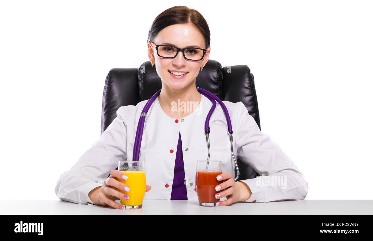 Female nutritionist sitting in her working place showing and offering glass of tomato and orange fresh juice on white background Stock Photo