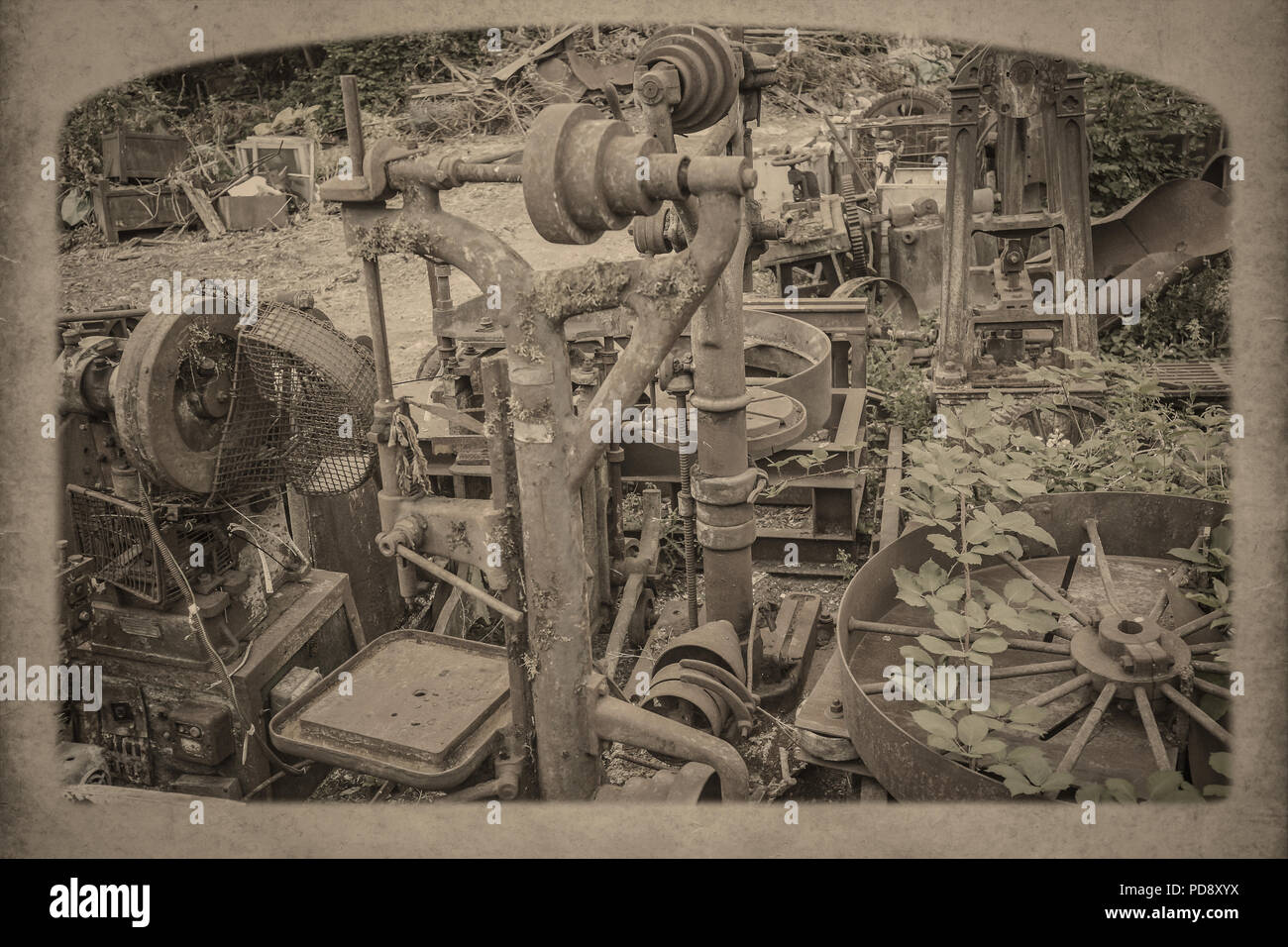 Arty, nostalgic, landscape shot of abandoned, neglected, industrial metalwork parts in outside setting, overgrown with weeds. Vintage sepia effect. - Stock Image