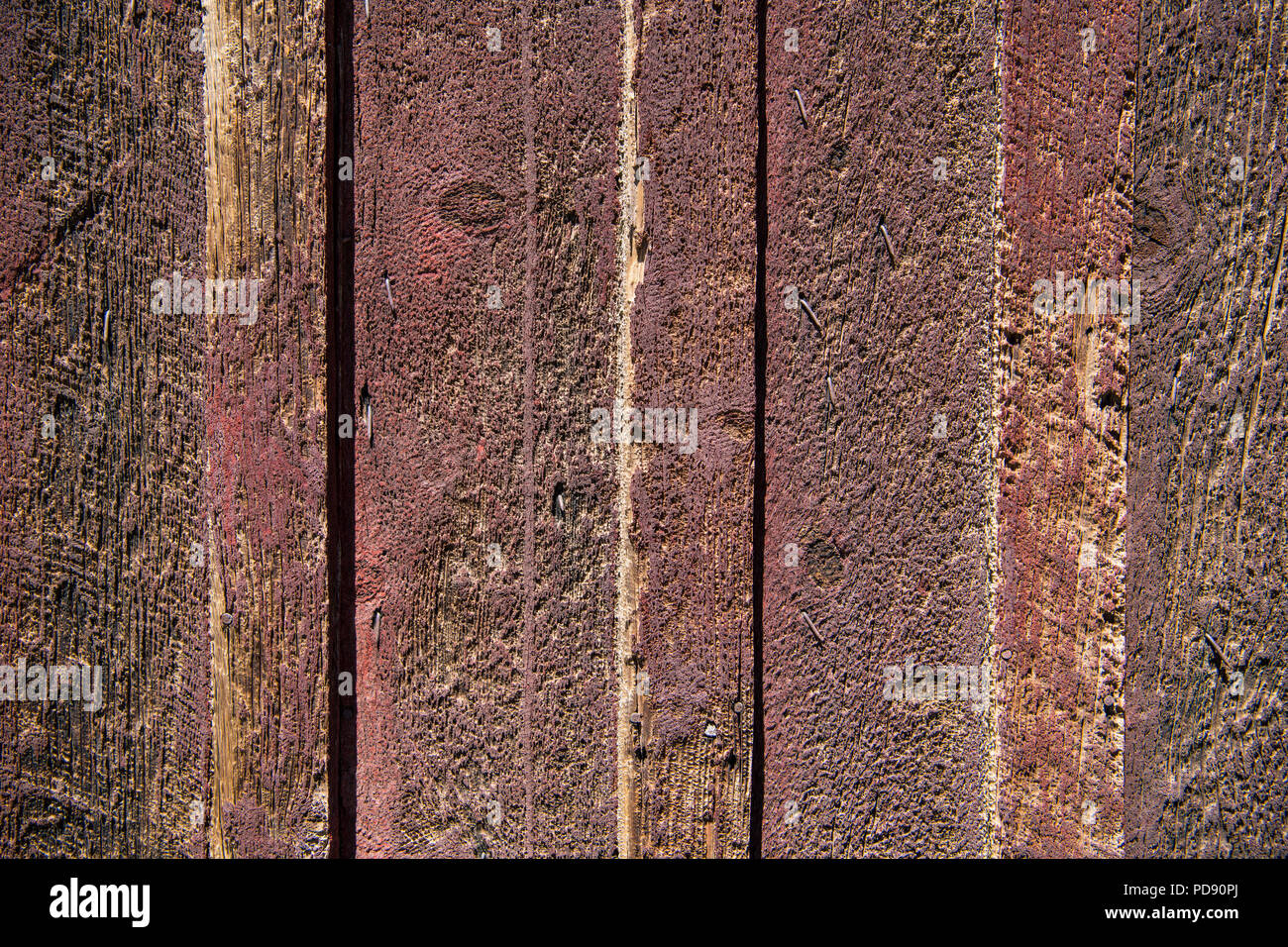 Rustic background texture of weathered rough cut wood boards with red and brown color tones - Stock Image