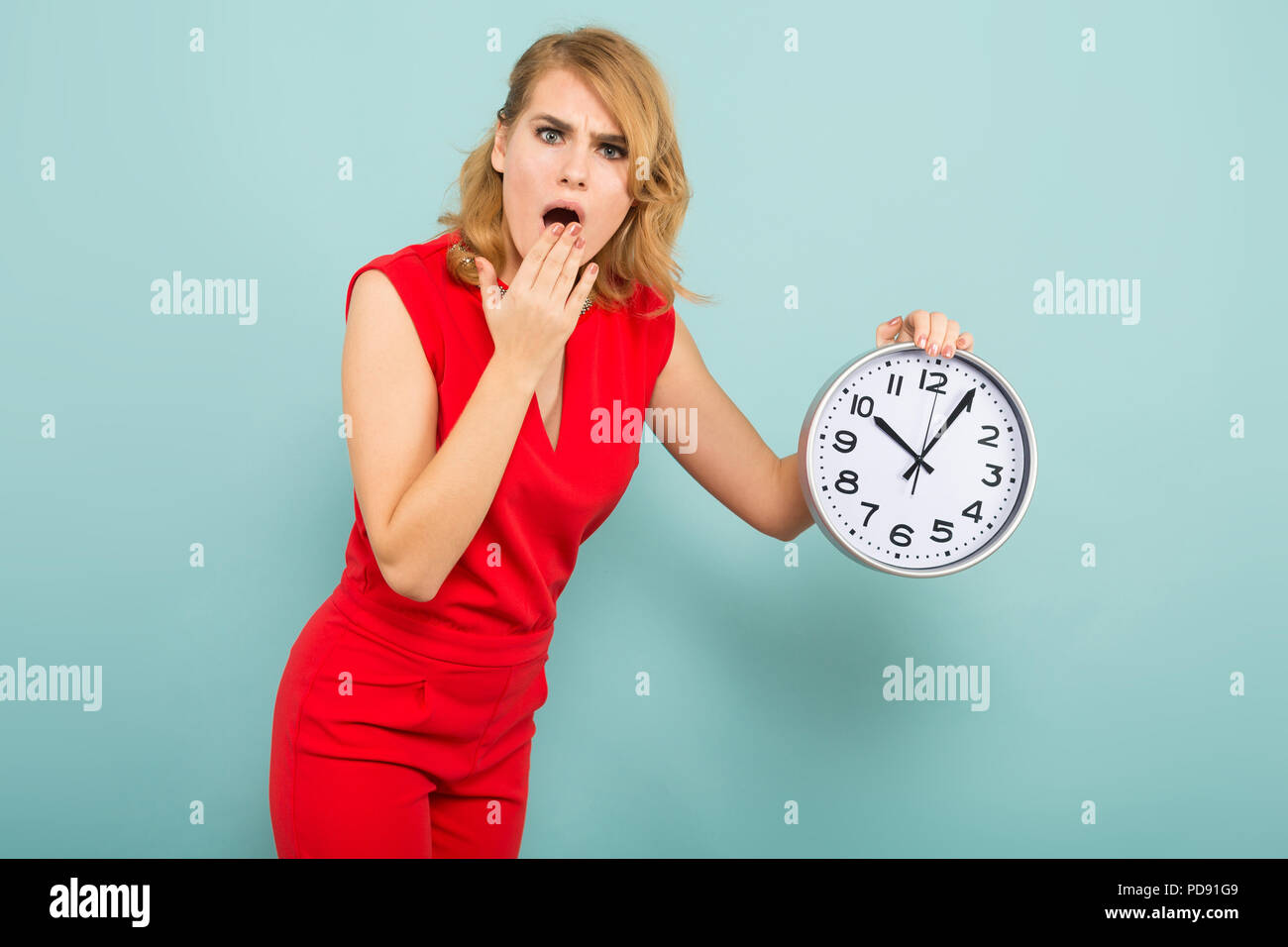 Attractive shocked woman with clocks - Stock Image