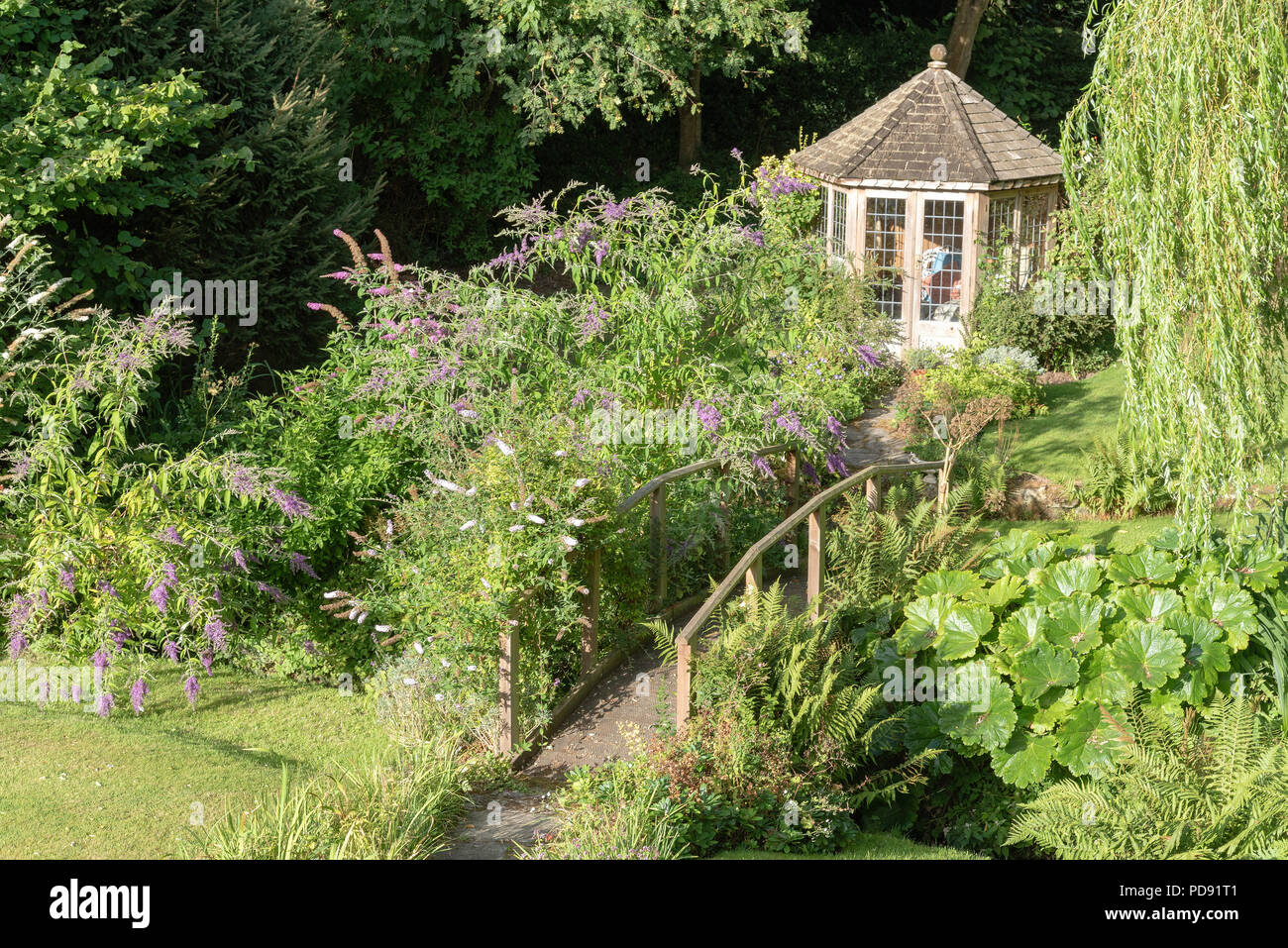 Overview of a summer house and wooden bridge in an English country garden - Stock Image