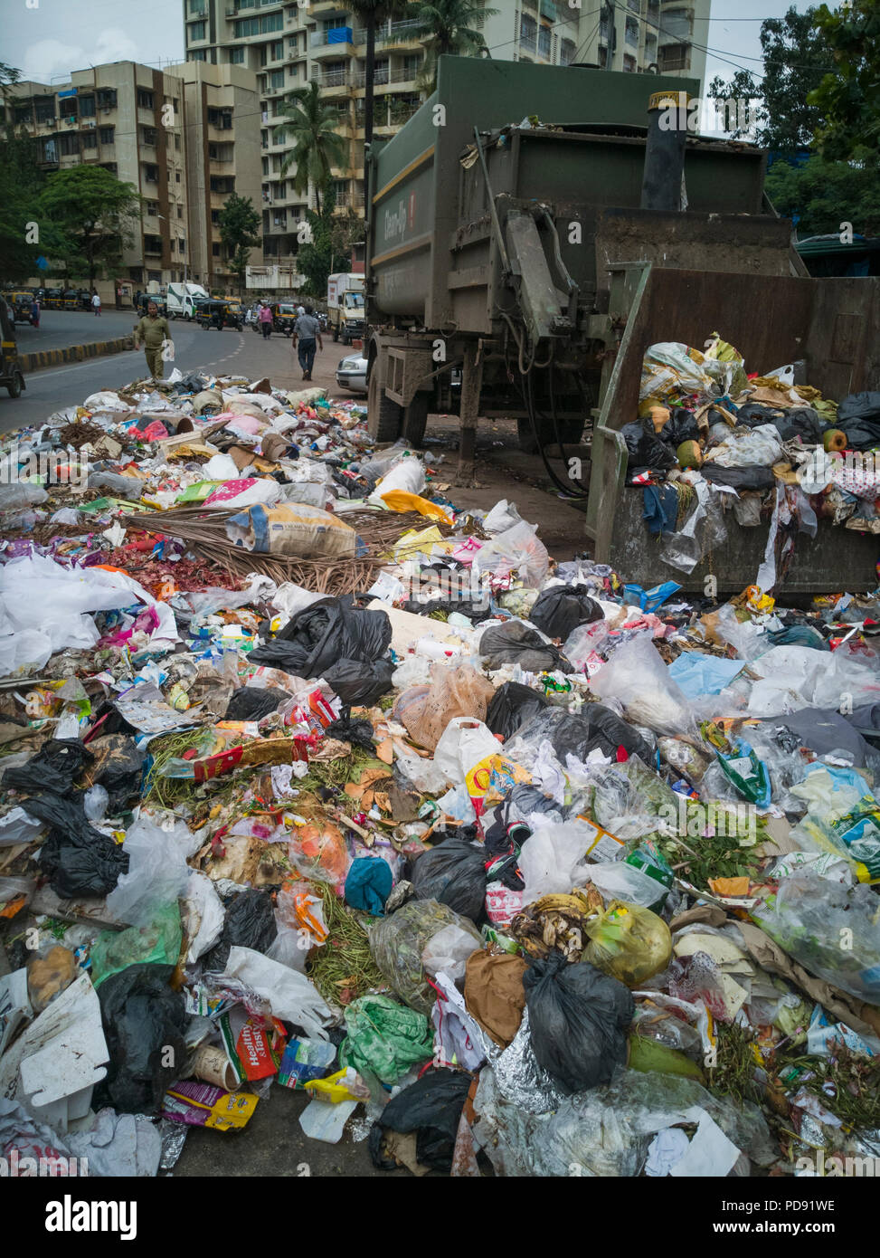 Plastic bags full of household rubbish lie on street next to dumpster in Mumbai, India Stock Photo