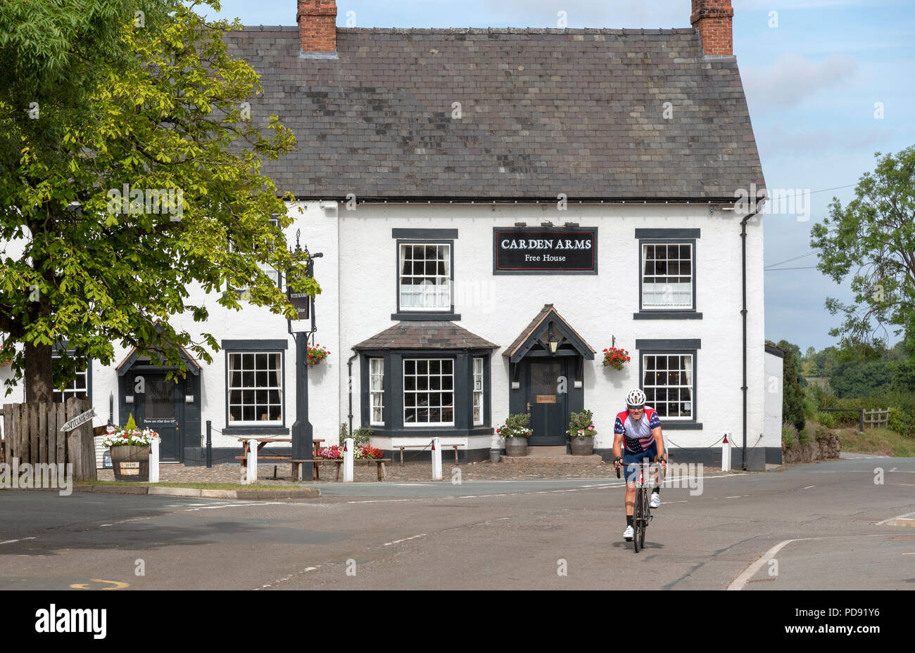 Carden Arms a 16th Century coaching Inn at Tilson, Malpas, Cheshire, England, UK. Exterior view with a cyclist passing by, - Stock Image