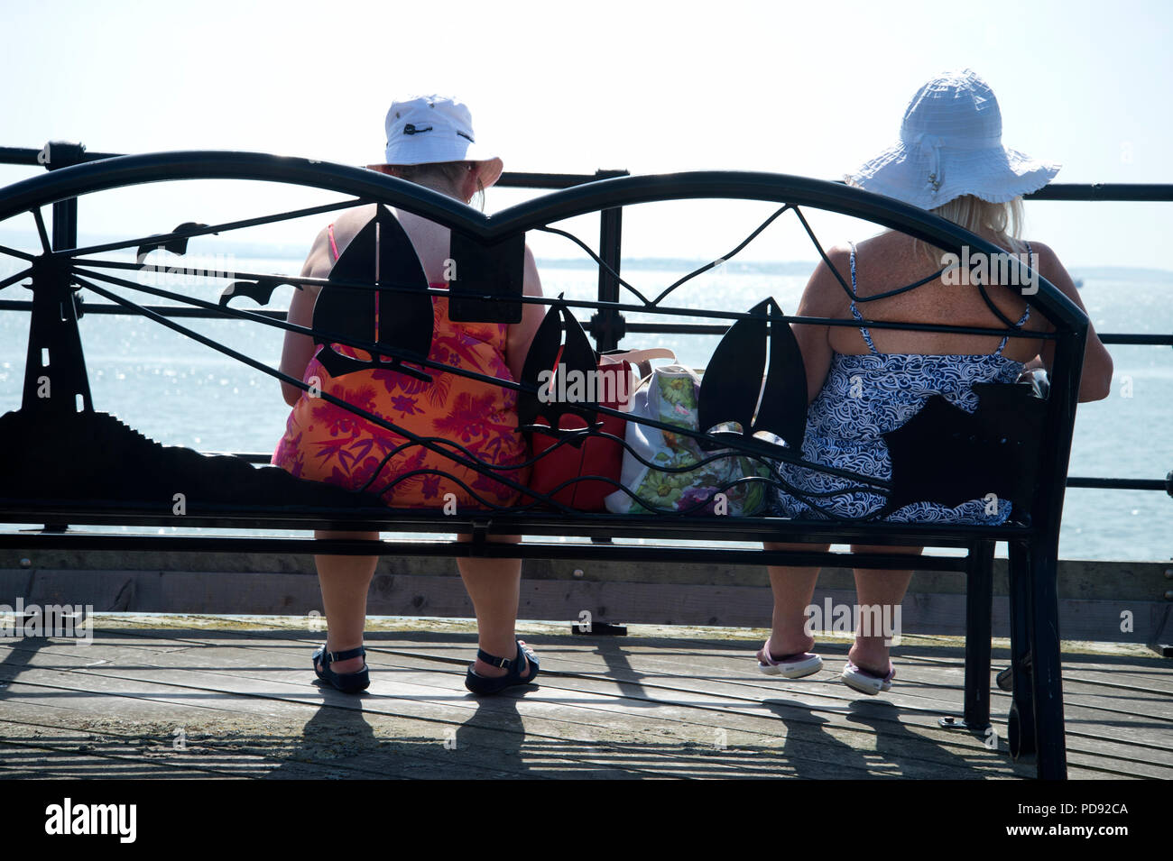 Southend on Sea, Essex. Two older women sit on a bench looking at the sea - Stock Image