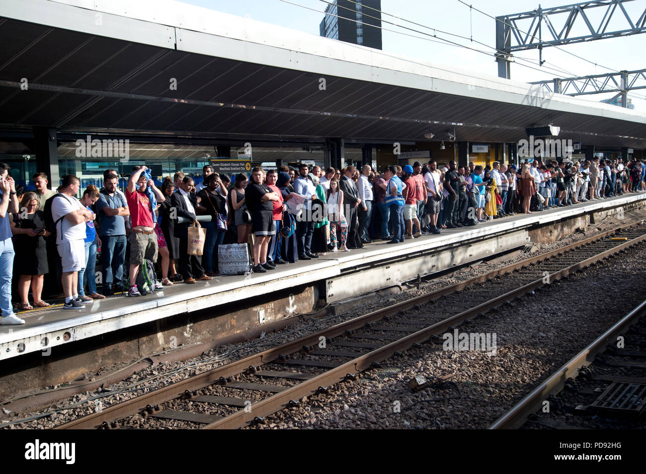 Stratford Station, London. Rush hour on a hot evening. Commuters wait for a delayed train to arrive - Stock Image