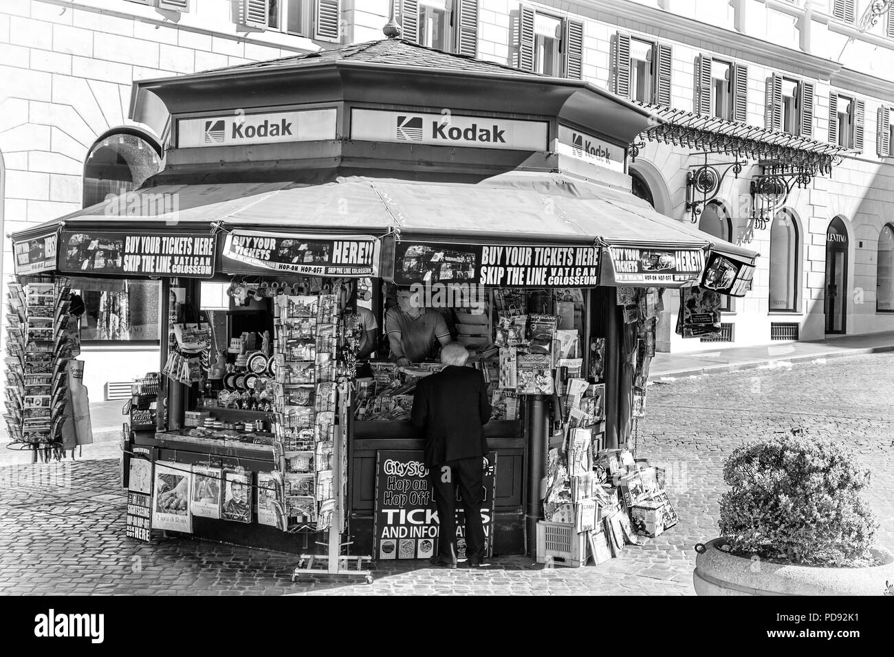 An elderly gentleman makes a purchase at a kiosk in Rome selling tourist goods - tickets, postcards, souvenirs, newspapers, magazines and Kodak film - Stock Image