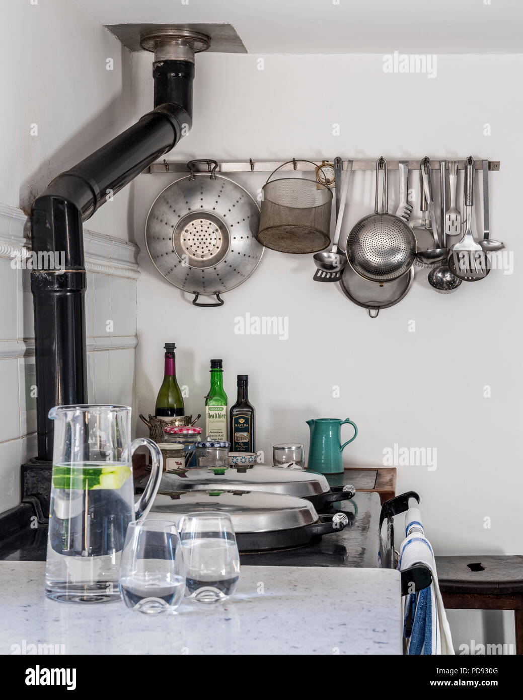 Cooking utensils hang from a rack above the Aga - Stock Image
