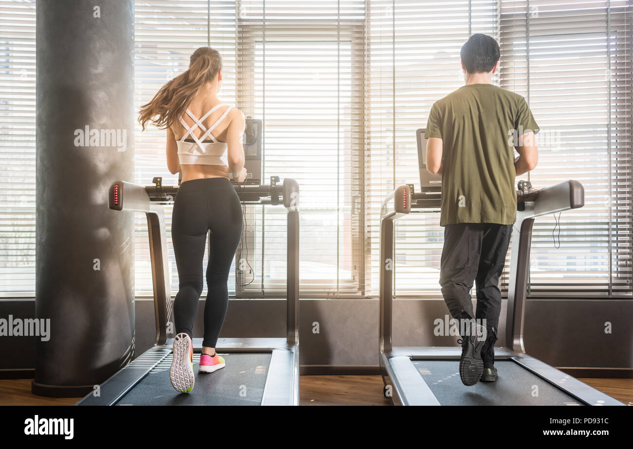 Young man and woman running on treadmills during workout - Stock Image