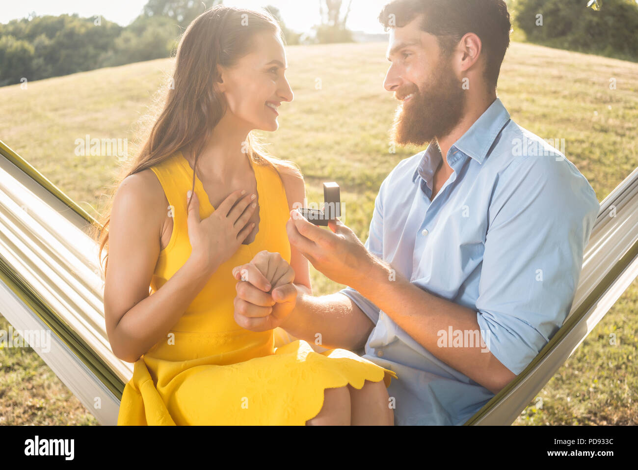 Young man making marriage proposal to beautiful girlfriend outdoors - Stock Image