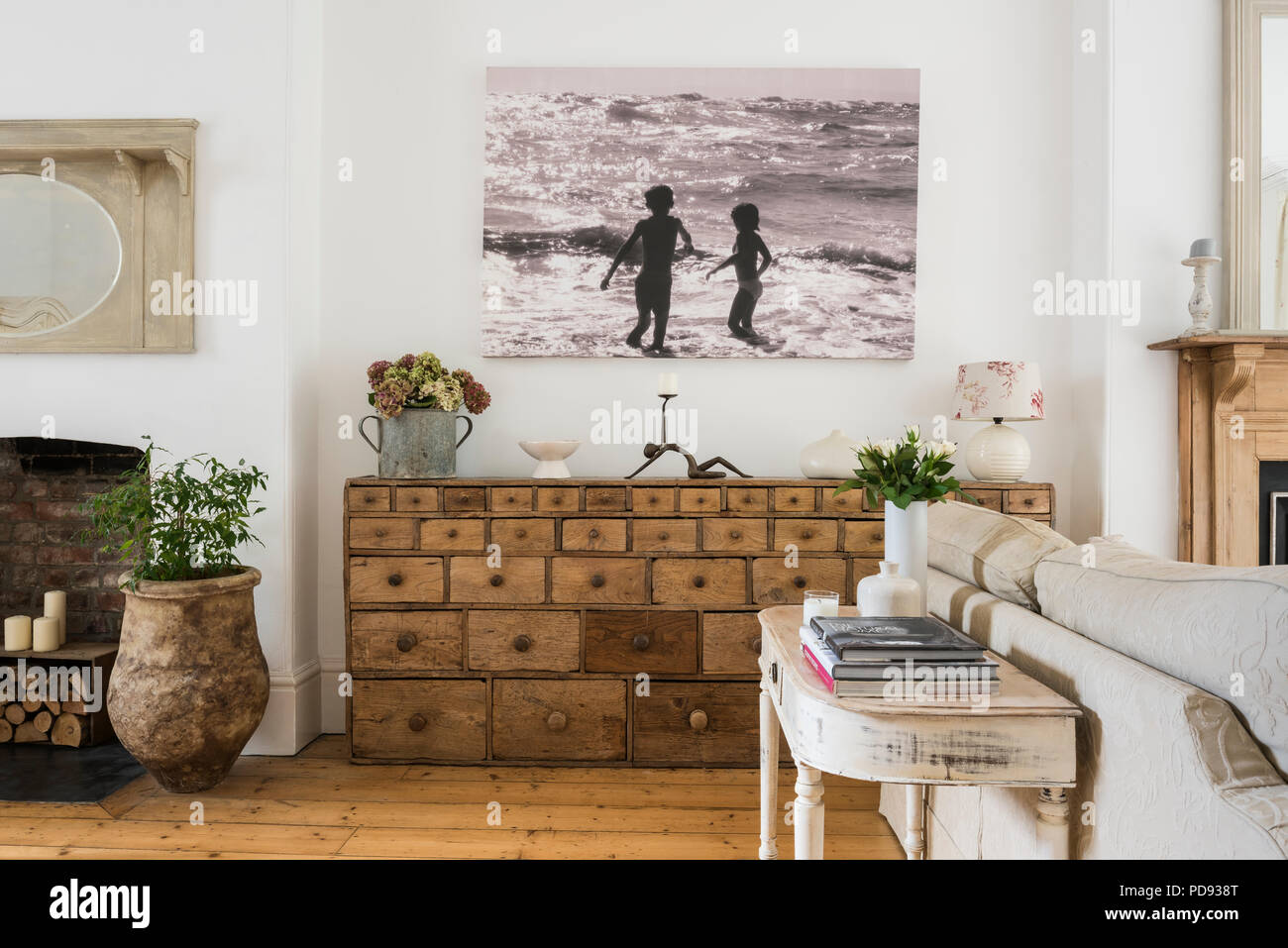 Large antique apothecary cabinet below a large photographic print in bright sitting room Stock Photo