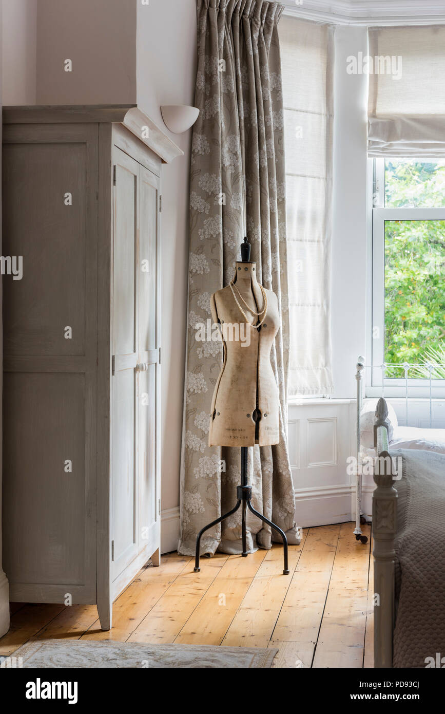 Vintage tailors dummy in airy bedroom with floor length printed curtains and wooden floors - Stock Image