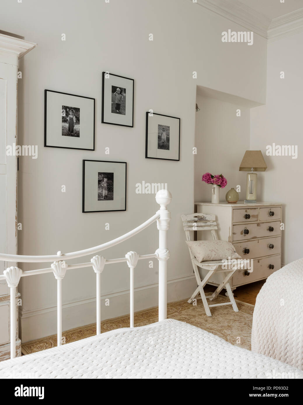 Black and white family photographs adorn the wall of a guest bedroom with old chest of drawers and quilt bed throws - Stock Image