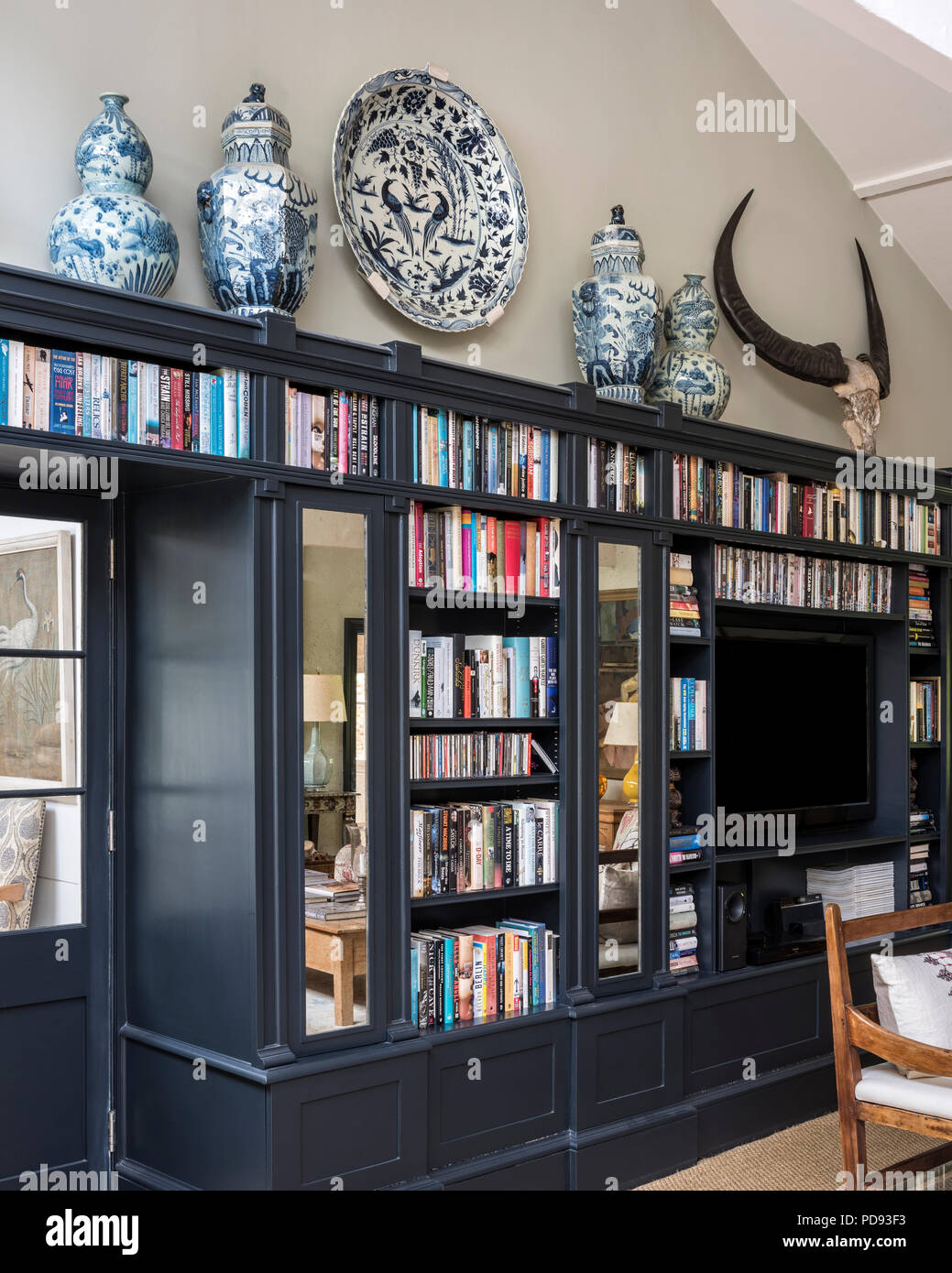 Blue and white pots on top of Farrow and Ball Downpipe, painted book shelves - Stock Image