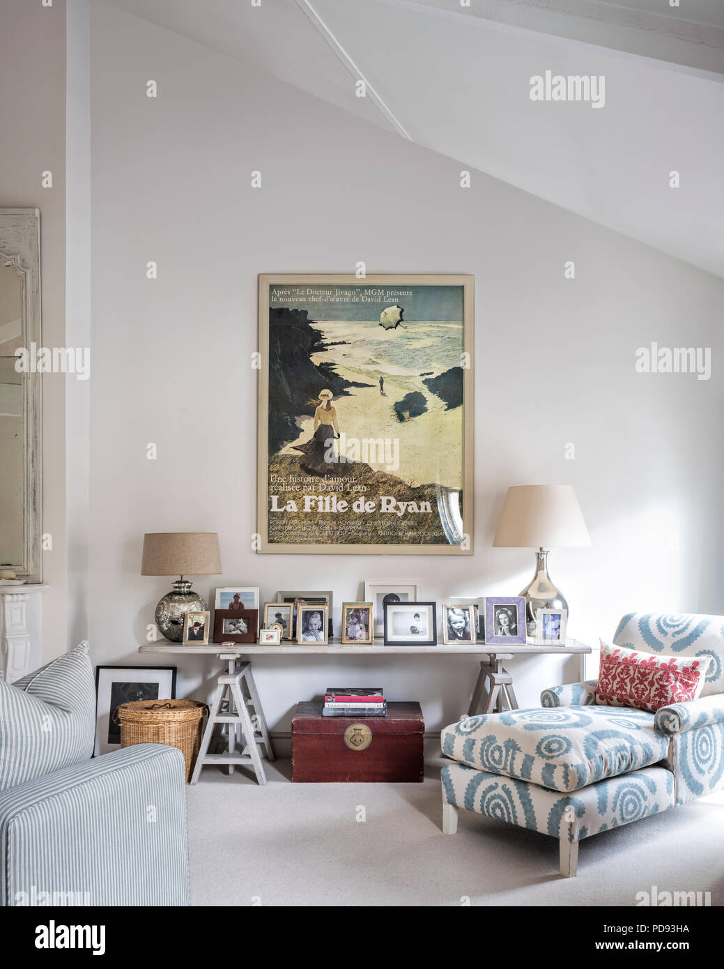 A large vintage film poster on wall of bedroom. The chaise is upholstered in printed linen from Penny Morrison - Stock Image