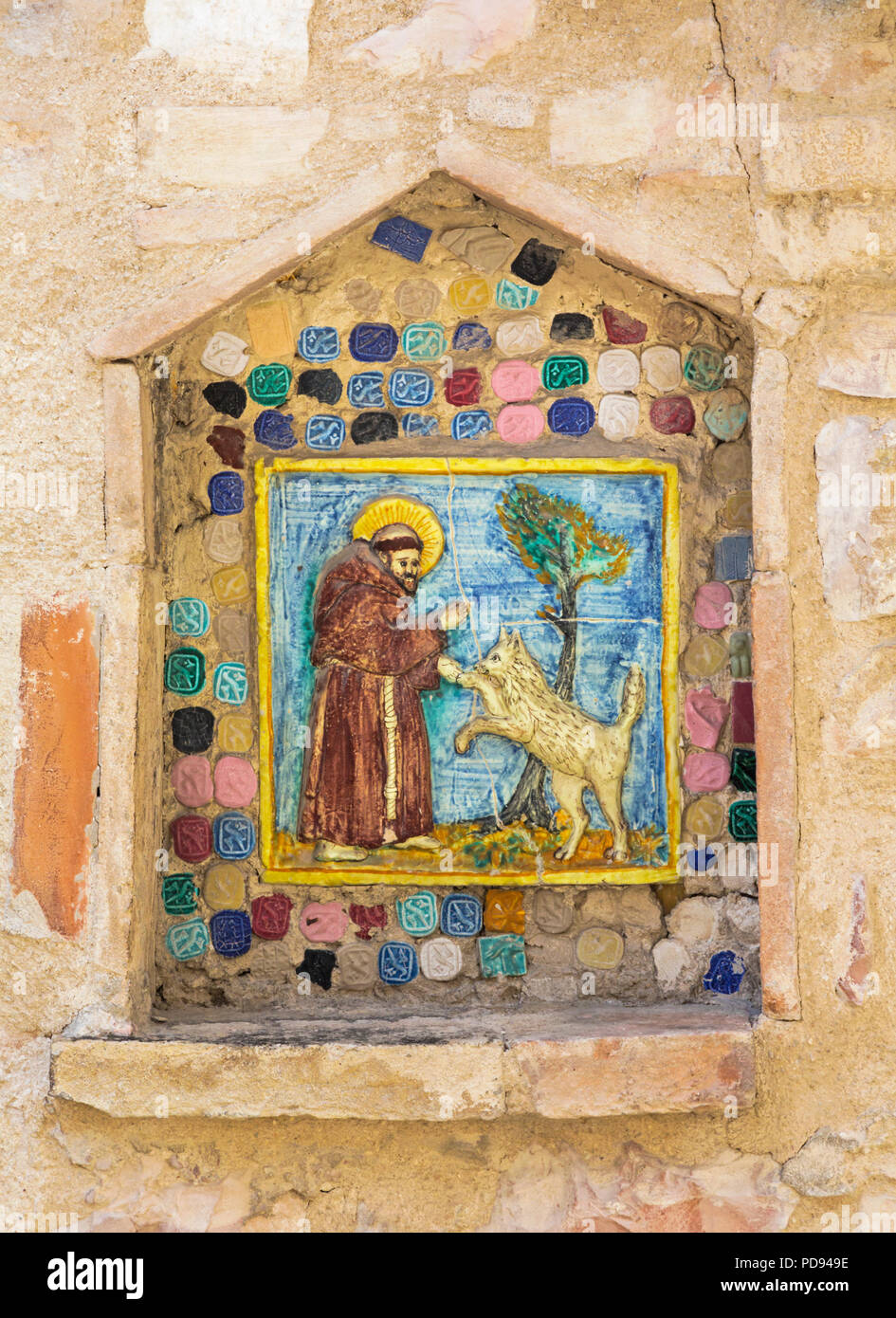 Assisi, Perugia Province, Umbria, Italy.  Ceramic tile of St. Francis of Assisi blessing a dog or a wolf. - Stock Image