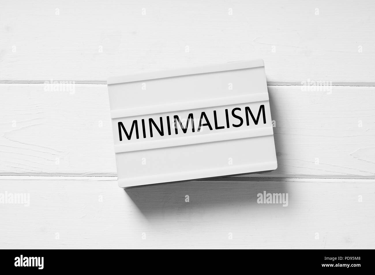 minimalism text on lightbox sign, minimal flat lay design on white wooden background, simplicity concept - Stock Image