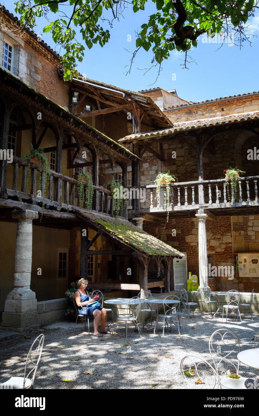 A tourist sitting in the courtyard, Maison des Vins, Bergerac Old Town, Dordogne, France Europe - Stock Image