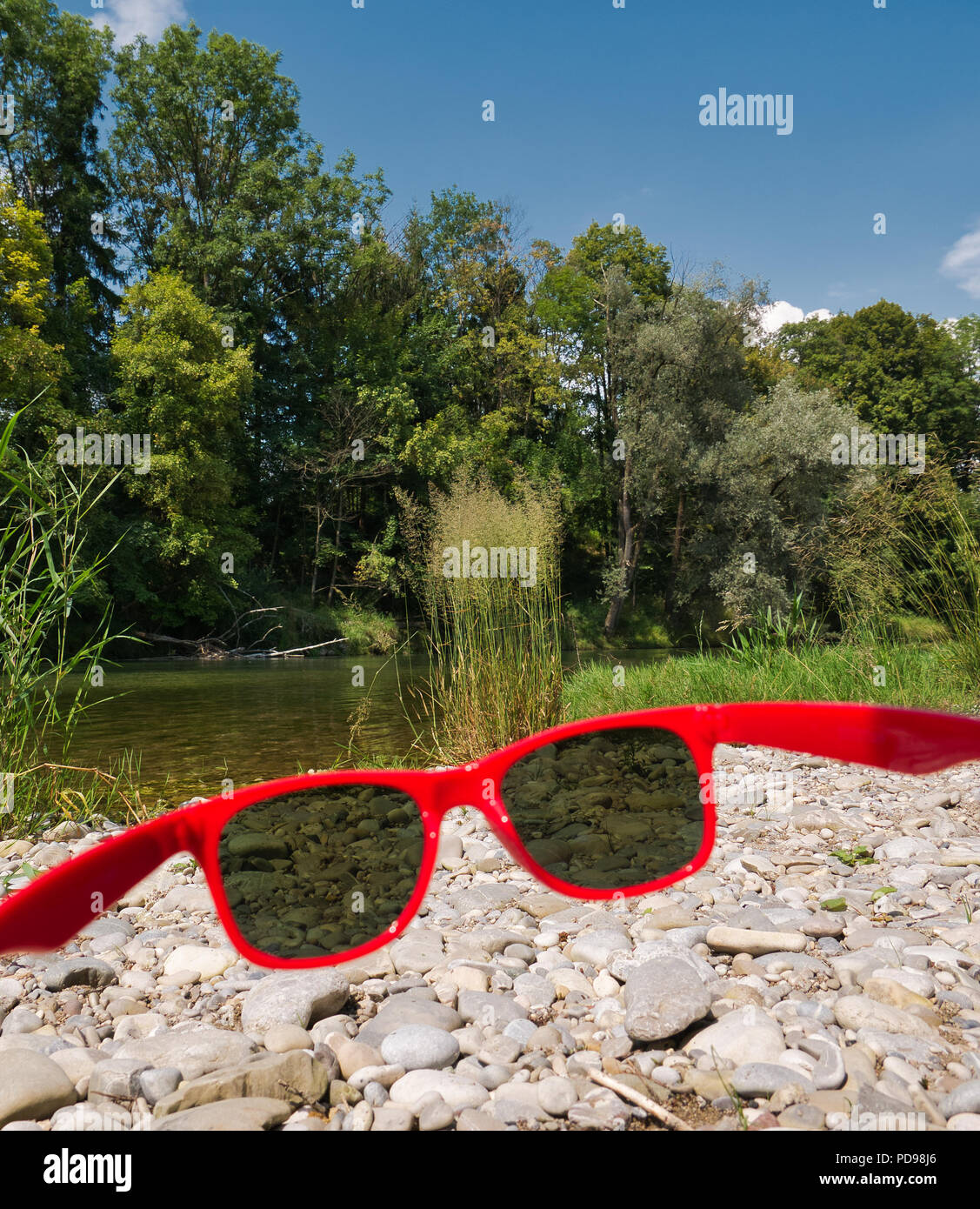 Looking through a red sunglasses at the stones on the bank of the river Isar in Munich with trees in the background - Stock Image