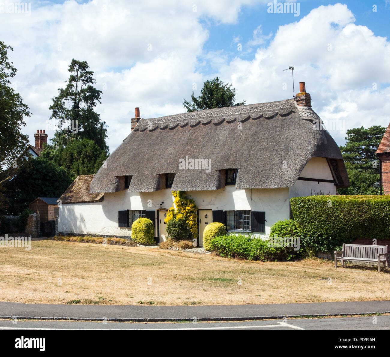 English country cottage with thatched roof on the village green in the village of Cuddington Buckinghamshire England UK - Stock Image