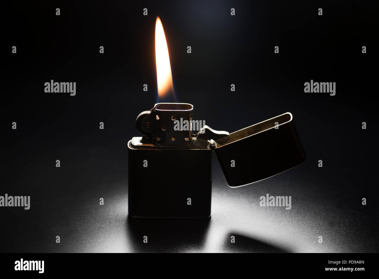 Zippo lighter with yellow flame isolated on black background. - Stock Image
