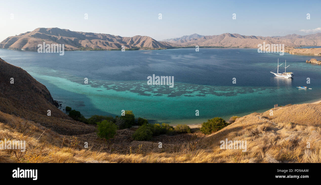 The arid islands in Komodo National Park, Indonesia, are surrounded by beautiful fringing coral reefs. This area is known for its dragons and reefs. - Stock Image