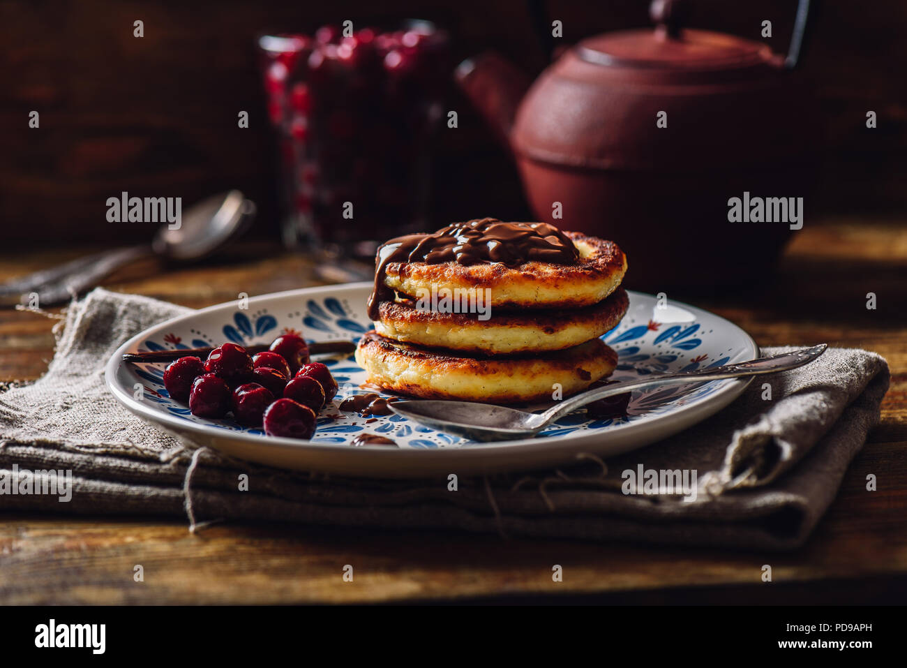 Breakfast with Quark Pancakes with Chocolate Paste and Frozen Cherry. Tea Pot with Spoons and Glass of Berries on Background. - Stock Image