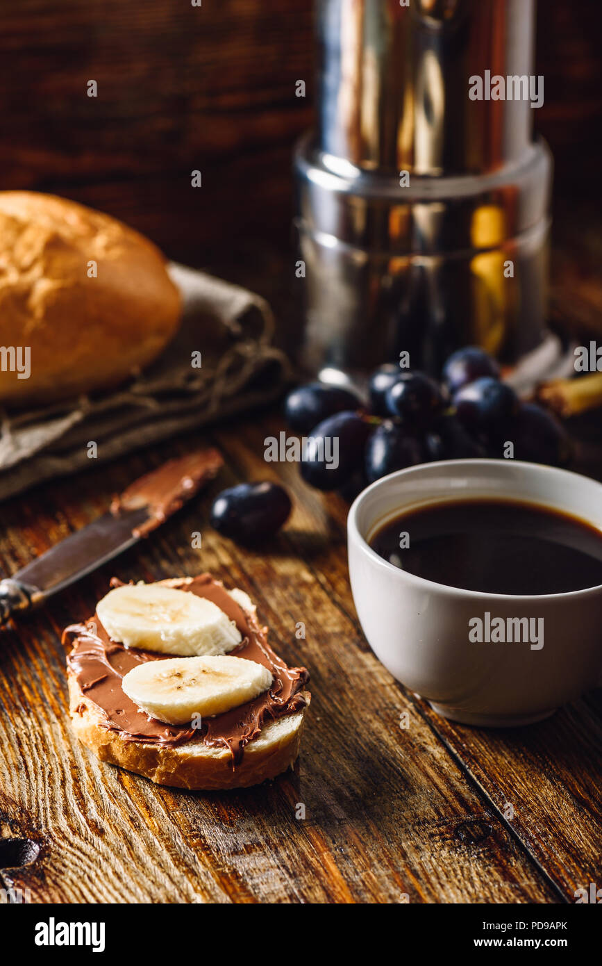 Breakfast with Banana Sandwich with Chocolate Spread, Coffee Cup and Grapes. Vertical Orientation. - Stock Image