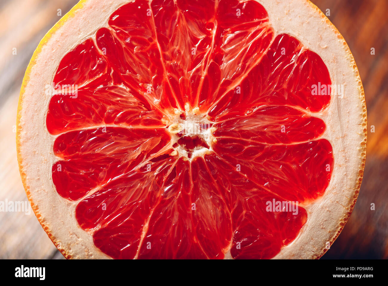 Half of Ripe and Juicy Grapefruit on Wooden Table. Stock Photo