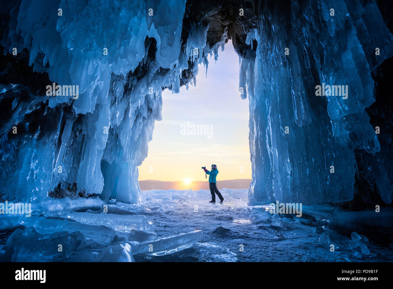 Unknown tourist in front of ice cave on Olkhon island at Baikal lake in Siberia during winter. - Stock Image