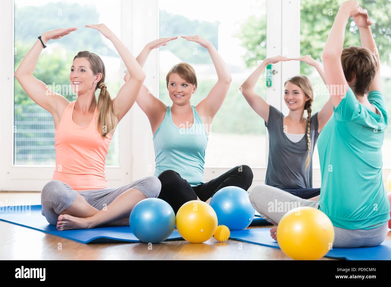 Moms in postnatal regression course doing yoga asana - Stock Image