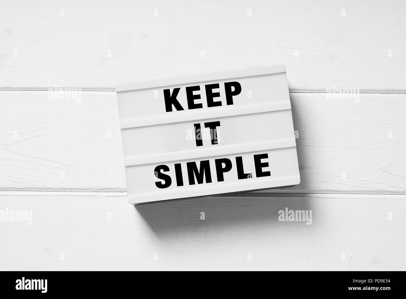 keep it simple text on lightbox sign, minimal flat lay design on white wooden background, simplicity or minimalism concept - Stock Image