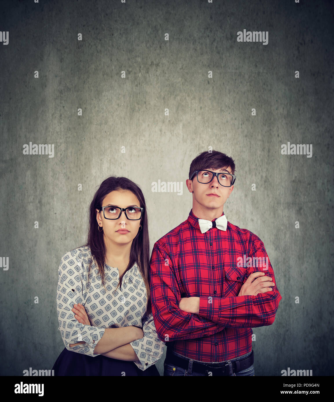 Young man and woman in glasses standing together with hands crossed and looking up being grumpy and having confrontation - Stock Image