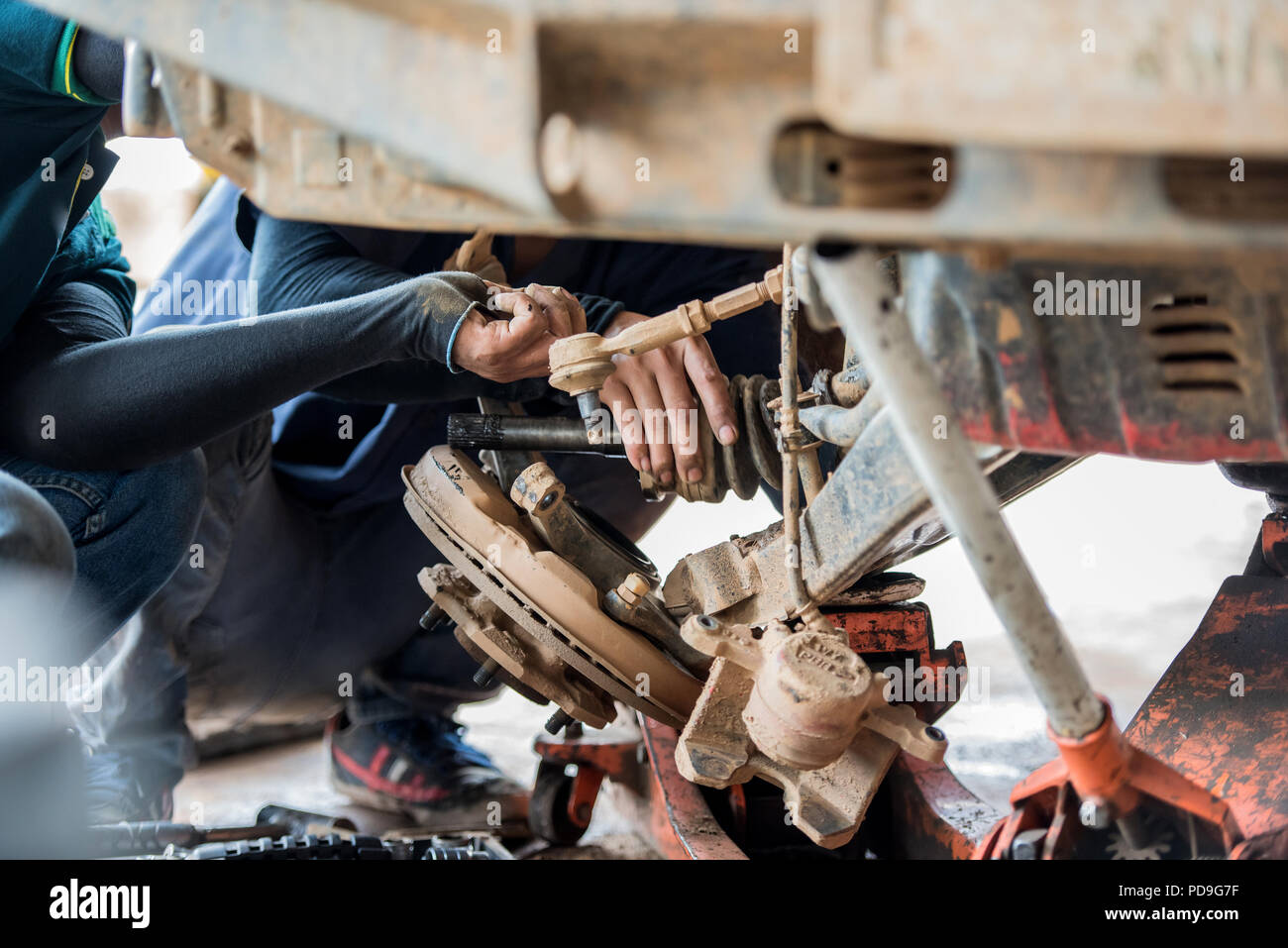 Technician disassemble the driving shaft of the car in the garage - Stock Image