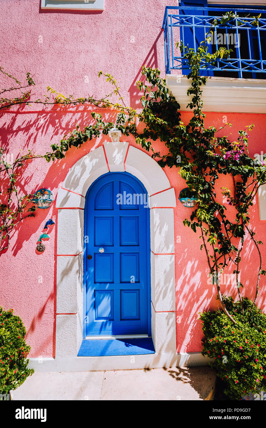 Assos village. Traditional lilac colored greek house with bright blue door and fucsie plant flowers around. Kefalonia island, Greece - Stock Image