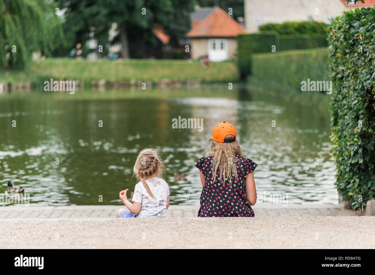 Young girls feeding birds by the city pond. Throwing bread to ducks. Pretty colorful dresses and skirts, long hair. - Stock Image