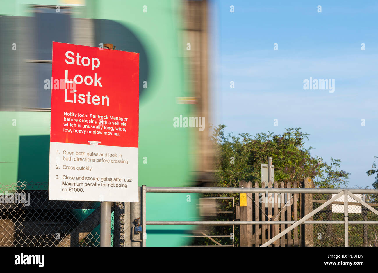 Unattended pedestrian railway train crossing with Stop, Look, Listen warning sign and a Southern train speeding past in West Sussex, England, UK. - Stock Image