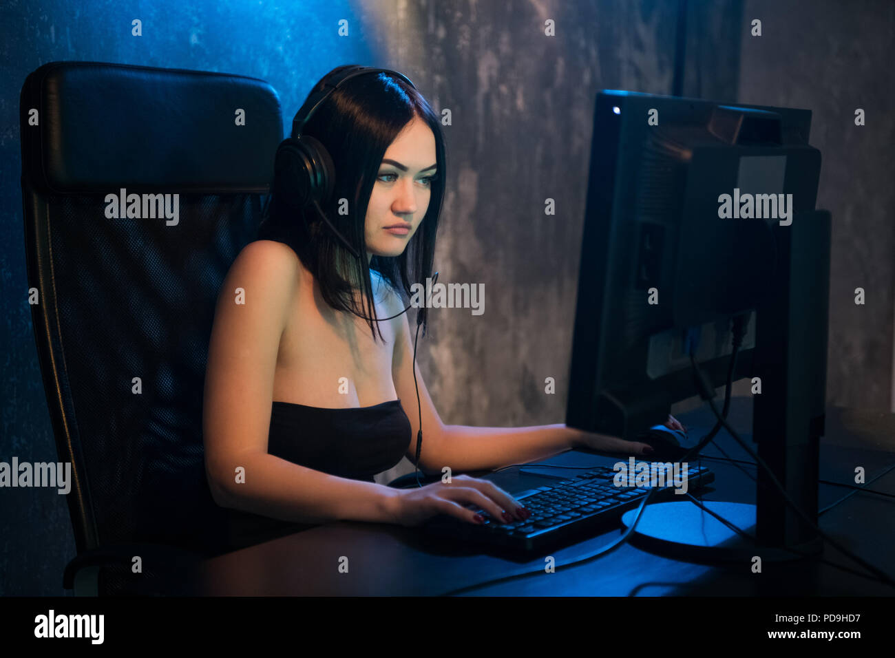 Young attractive woman playing video games on her computer wearing gaming headset. - Stock Image