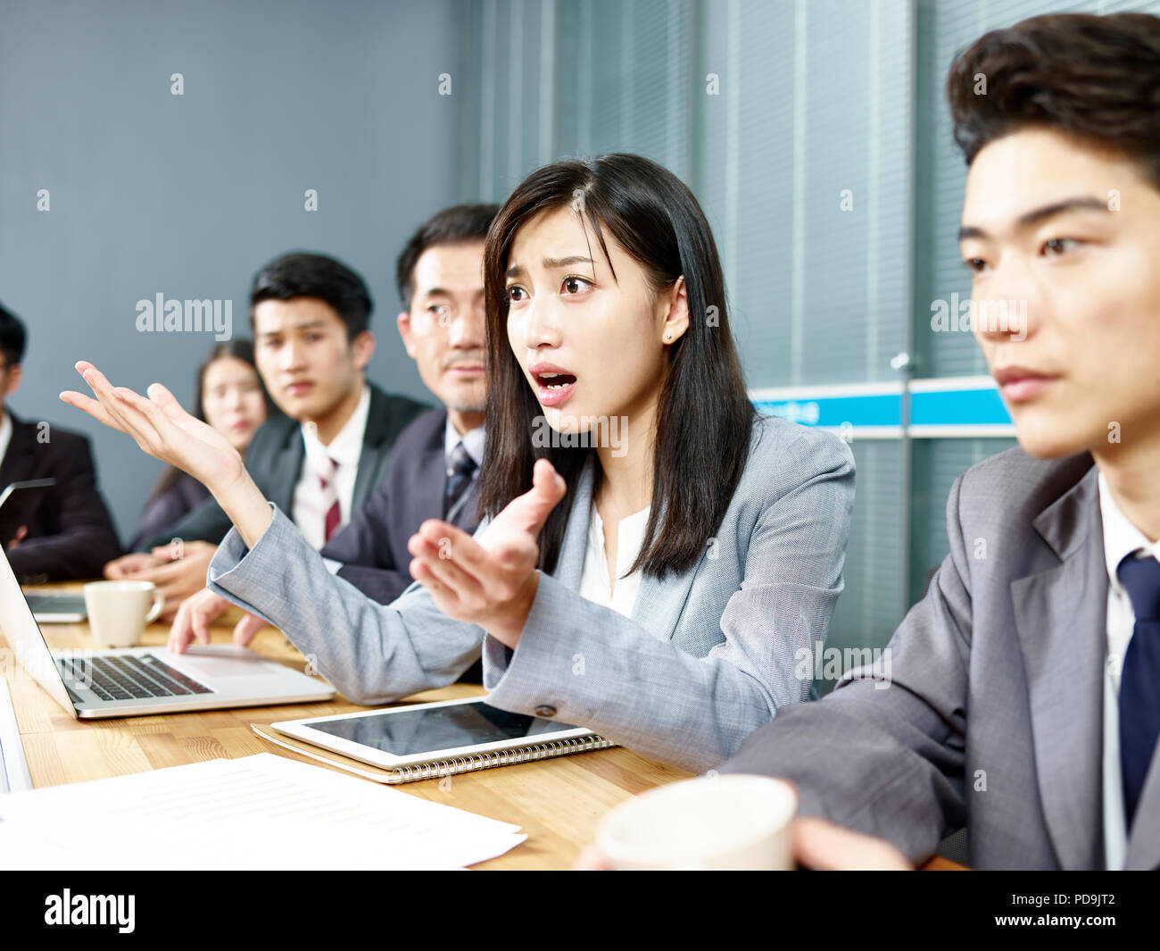 young asian business woman executive engaging in a heated discussion during meeting. - Stock Image