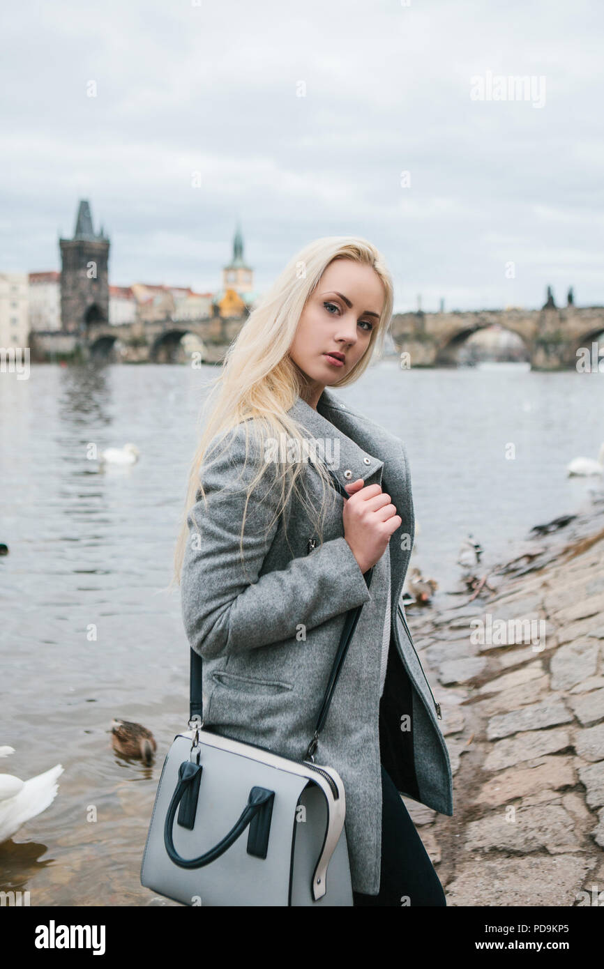 Fashionable blonde with long hair in a coat near Charles Bridge in Prague. Beautiful young woman outdoors. - Stock Image