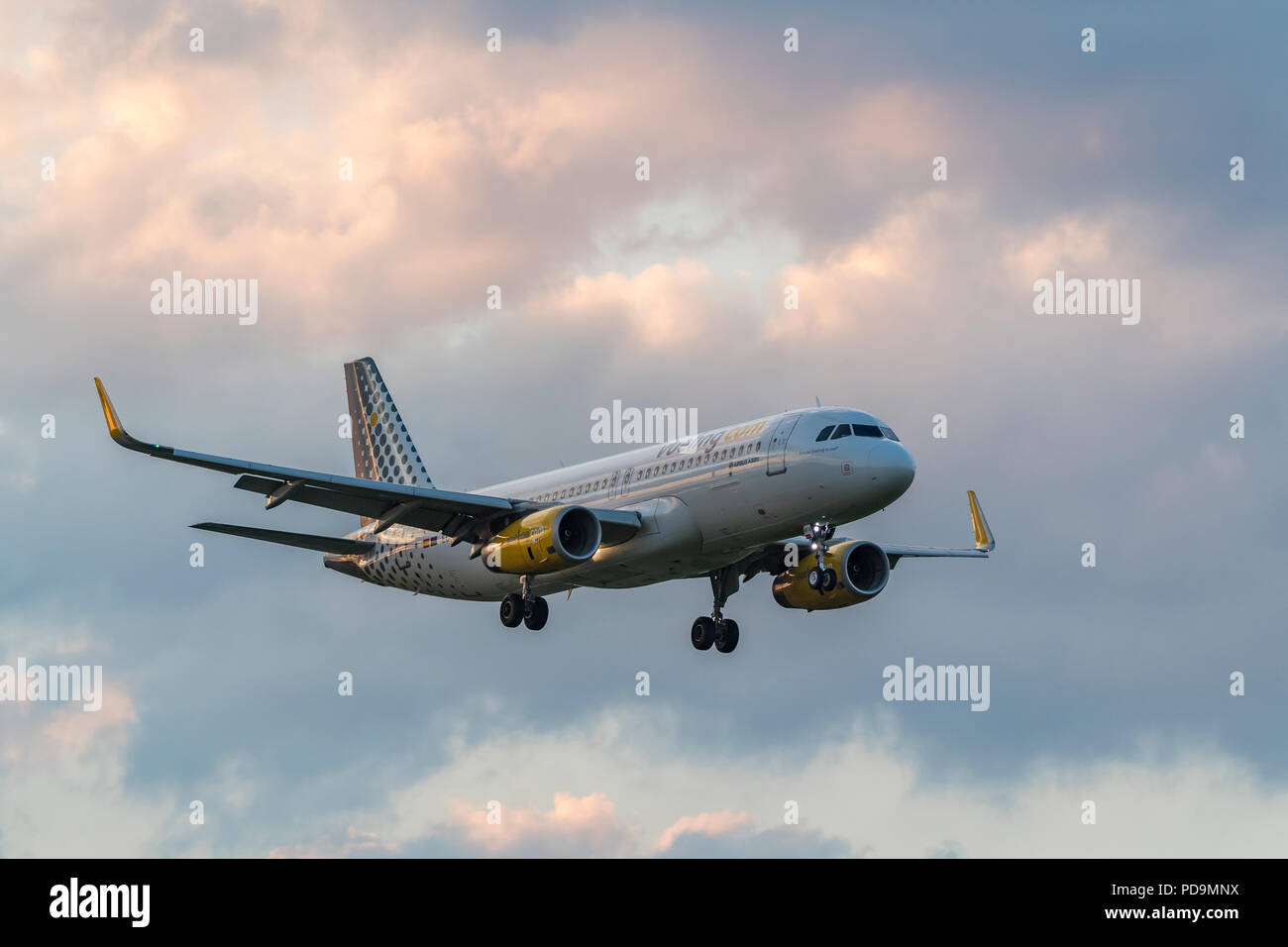 Airbus A320-323 of the airline Vueling during landing approach, cloud sky, Switzerland - Stock Image