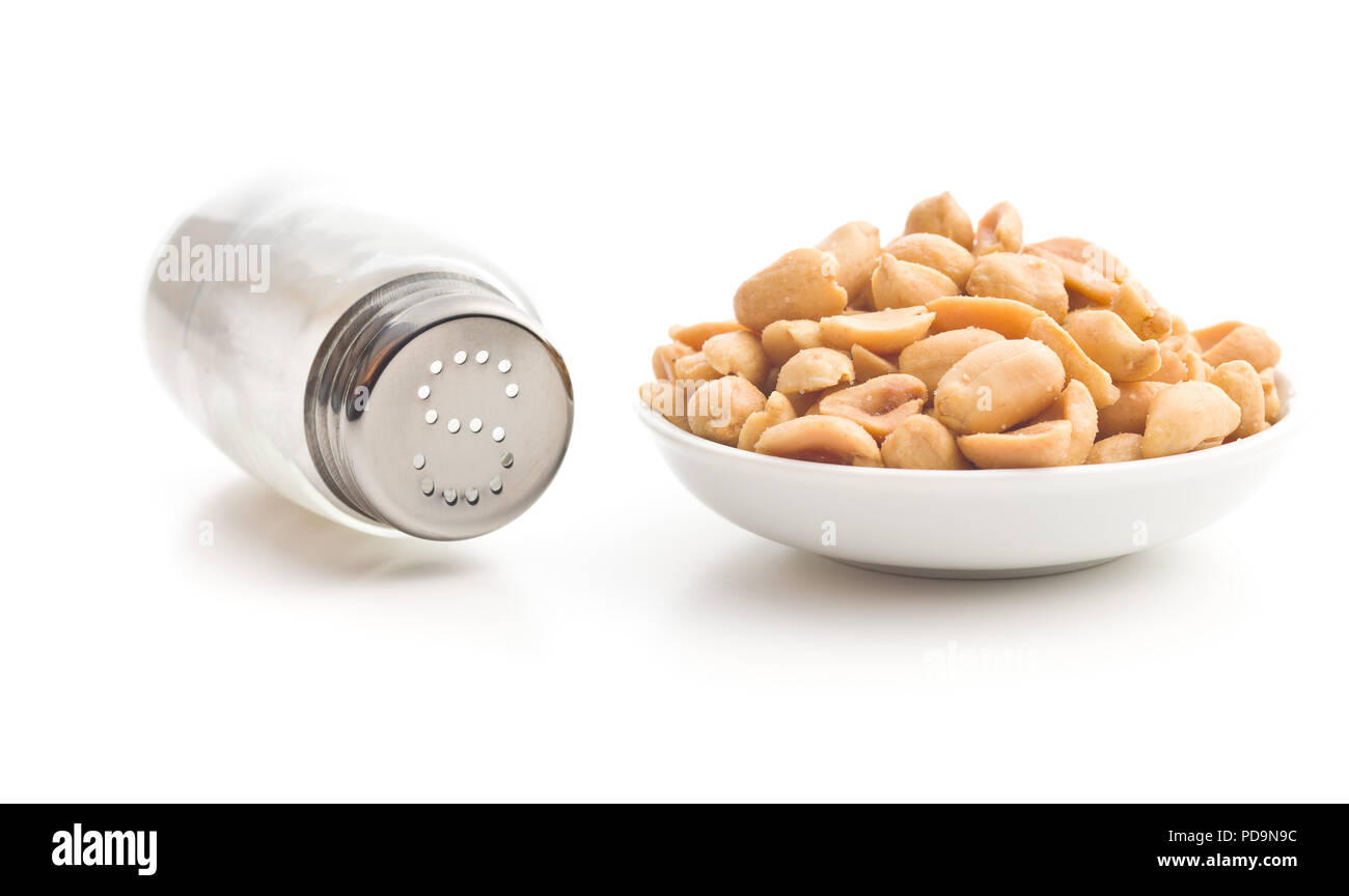 Salted roasted peanuts and salt cellar isolated on white background. - Stock Image