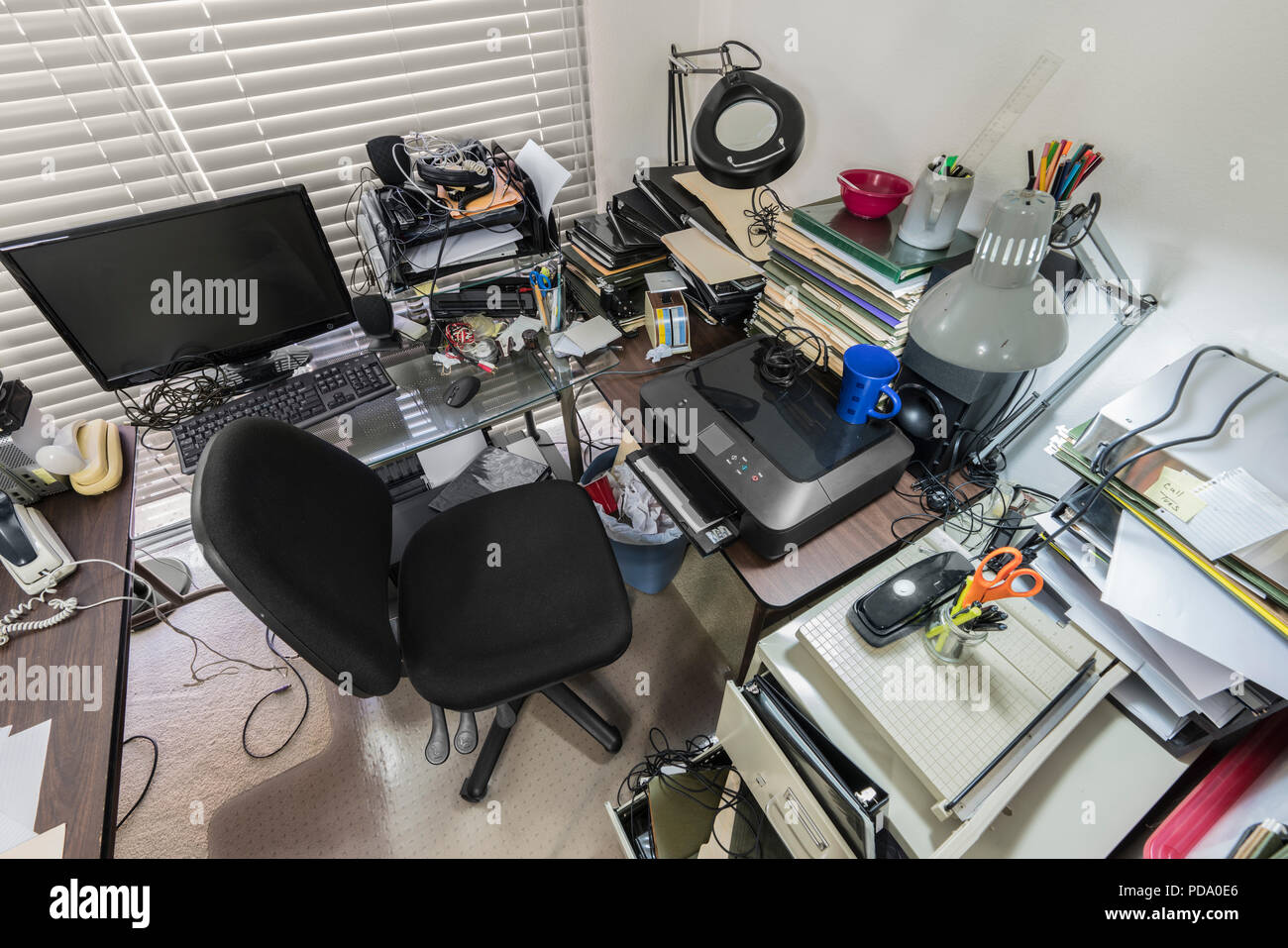 Messy office desk with stacks of files and disorganized clutter. - Stock Image
