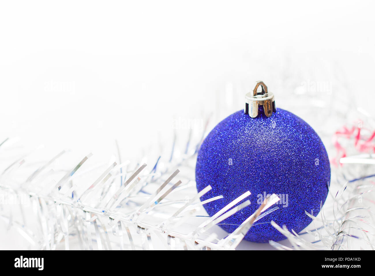 holidays winter and celebration concept christmas and new year card with blue ball and silver tinsel on white background copyspace