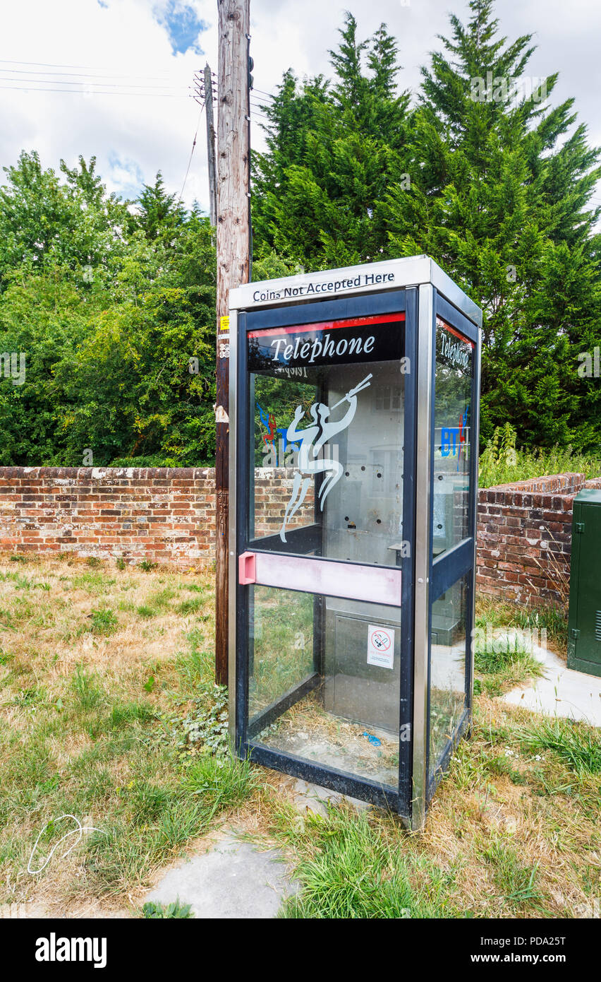 Useless old, disused BT telephone box with phone removed in Little Bedwyn, a small rural village in Wiltshire, southern England in summer - Stock Image